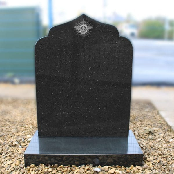 Black cemetery headstone with etched bird design