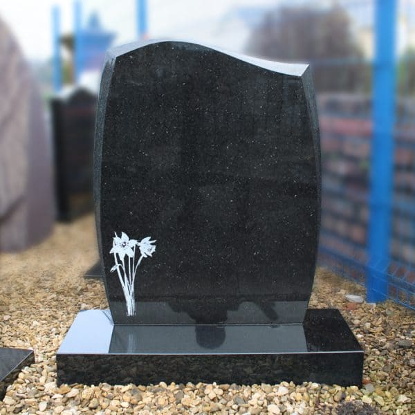 Black granite cemetery headstone with etched daffodil design