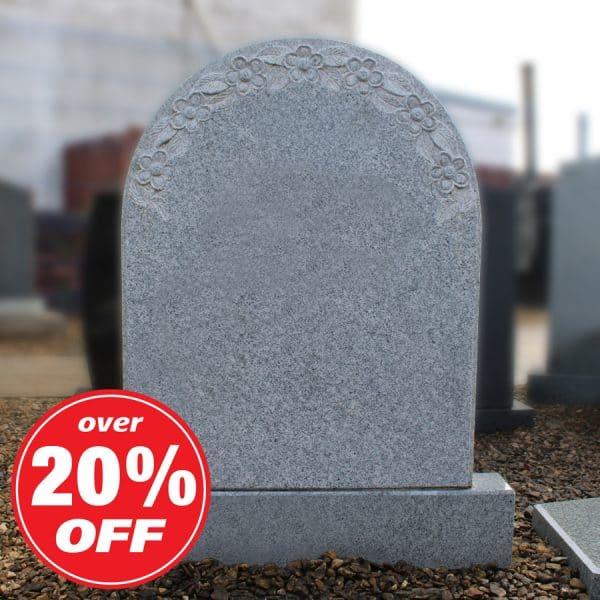 Grey rounded headstone with engraved flower design